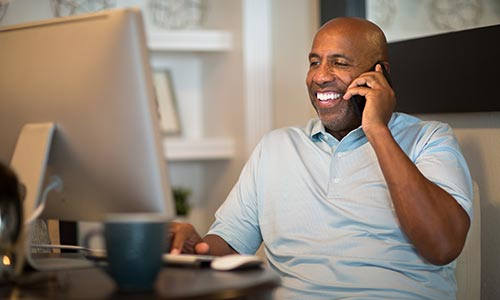 Happy man on the phone in front of his computer